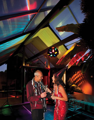 With colors swirling, Conny (left) and Andrea Marx sip their drinks to the disco ball and music under the retractable roof of their Eichler atrium.