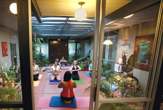 "Prabha Gopal (in red) leads students during a session of ""serious, classical yoga"" in her Walnut Creek Eichler."