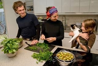 The Brix-Bayer family gathers in the kitchen for dinner preparation (L-R): Carl, Martina, Vitus, and kitty.