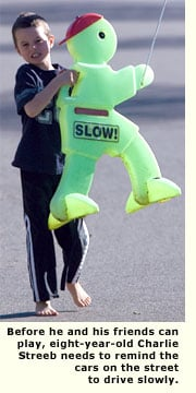 young boy puttng out slow down sign